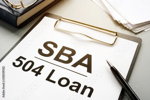 SBA 504 loan agreement form and clipboard.