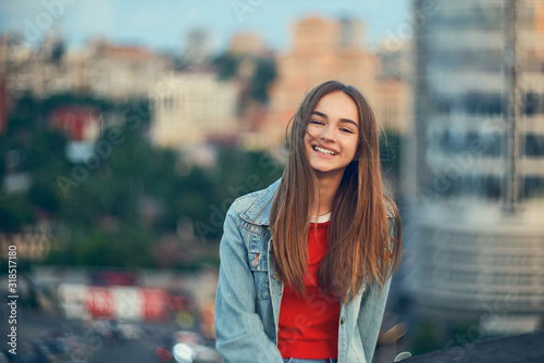Vászonkép Lovely teen girl on cityscape background