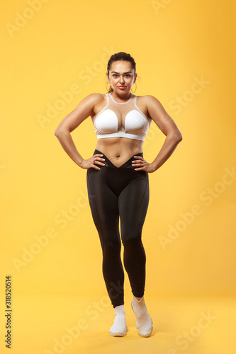 Vászonkép Size plus woman sporty fit woman in sportswear, athlete makes fitness exercising on yellow background