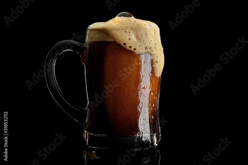 Платно Cold beer mug with black stout covered with drops and froth studio shot on black background