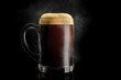 canvas print picture - Beer mug glass with black porter beer inside with drops, froth and vapor on black background.