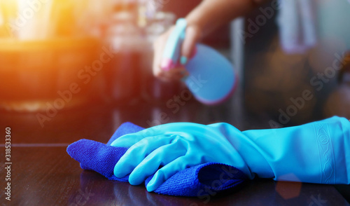 Obraz hand in blue rubber glove holding blue microfiber cleaning cloth and spray bottle with sterilizing solution make cleaning and disinfection for good hygiene - fototapety do salonu