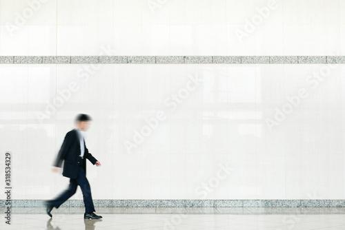 ビルの中を歩くビジネスマン Canvas-taulu