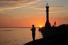 Silhouette Man Fishing By Sea Against Sky During Sunset
