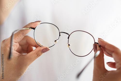 Obraz woman hand hand holding eyeglasses closeup ,healthcare and medical concept  - fototapety do salonu