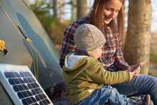 Little Wonderful Kid Takes The Phone From A Mother Sitting Near The Solar Panel At A Campsite In The Forest Under The Sun's Rays. Child Dressed In Jeans, Jacket And Hat In The Middle Of Warm Autumn