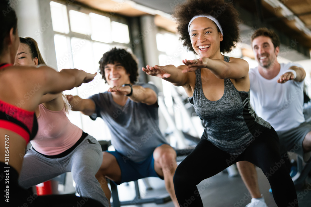 Fototapeta Group of healthy fit people at the gym exercising