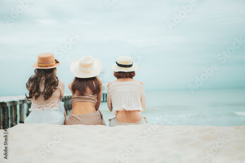 three woman wearing straw hat  sitting on vacation sea beach Fotobehang