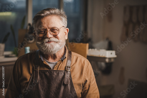 Photo happy, senior shoemaker in glasses smiling at camera while standing in workshop