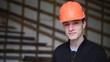Building constructor engineer wearing orange helmet smiling towards camera