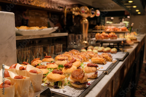Traditional spanish snacks, appetizers or tapas called pintxos in a bar counter in San Sebastian, Basque country, Spain Canvas Print