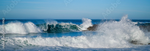 Foto Large ocean waves crash against coastal stones on sunny day on European coast