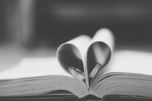 Close-Up Of Wedding Rings In Heart Shape Page On Book