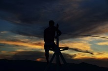 Silhouette Man Standing On Mast Against Sky During Sunset