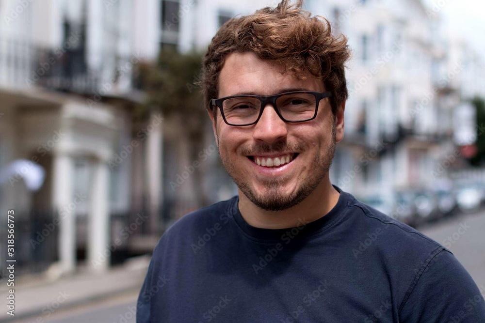 Fototapeta Portrait Of Happy Young Man Standing In City