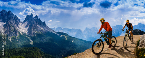 Photo Cycling woman and man riding on bikes in Dolomites mountains andscape