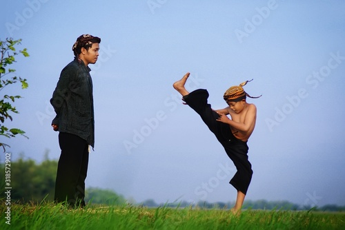 Fototapeta Male Instructor Watching At Boy Practicing Kung Fu On Field Against Sky