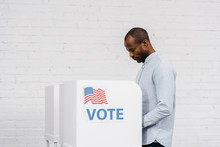 African American Citizen Voting Near Stand With Vote Lettering