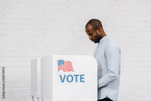Obraz na plátně african american citizen voting near stand with vote lettering