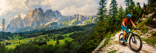 Fototapeta Tourist cycling in Cortina d'Ampezzo, stunning rocky mountains on the background