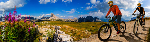 Cycling woman and man riding on bikes in Dolomites mountains andscape. Couple cycling MTB enduro trail track. Outdoor sport activity. - 318576968