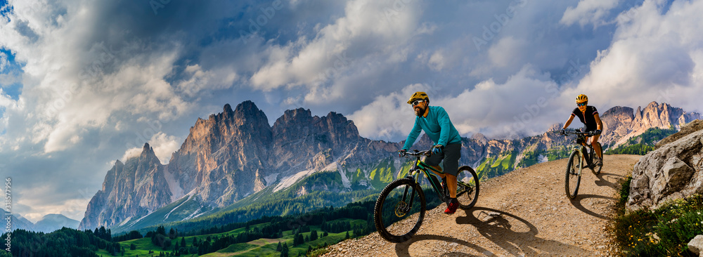 Fototapeta Cycling woman and man riding on bikes in Dolomites mountains andscape. Couple cycling MTB enduro trail track. Outdoor sport activity.