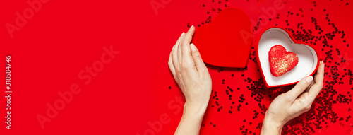 Woman hands holding red gift box shape of heart Heart Shaped Macaroon Cake confetti on red background top view Flat lay. Creative composition for Valentine's Day love concept birthday mother day