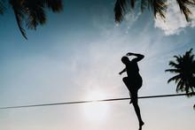 Man Slacklining On Rope Against Sky During Sunset