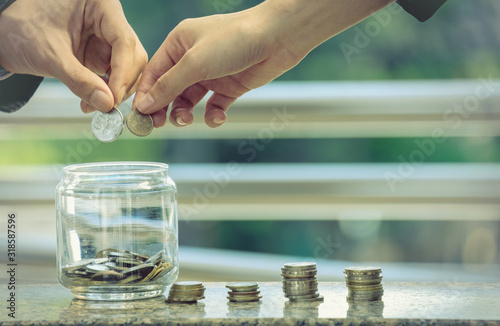 Fotomural  Cropped Hands Putting Coins In Jar