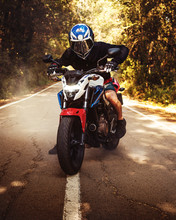 Guy On A Motorbike With Smoke Behind, Riding Forest, Agressive And Comercial. Transport And Summer Tour. Lifestyle And Outdoor.