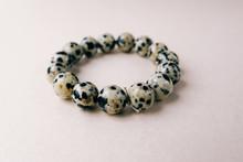 Gem Stone Dalmatian Jasper Bracelet Decoration Lies On Golden Background. Fashion Accessory Bead Stringing Hand Decoration. Handmade Woman Jewellery.