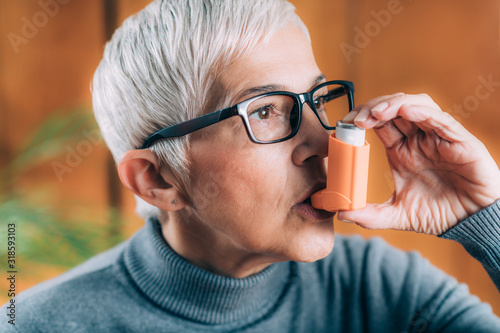 Senior Woman Inhaling Medicine from Asthma Pump Wallpaper Mural