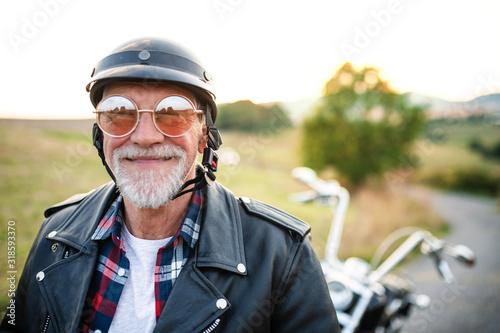 Radosny starszy podróżnik z motocyklem na wsi, headshot.
