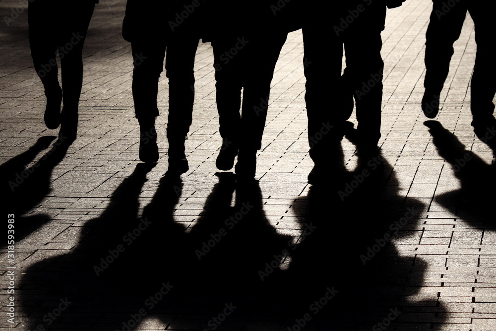 Fototapeta Silhouettes and shadows of people on the street. Crowd walking down on sidewalk, concept of strangers, crime, society, epidemic, population