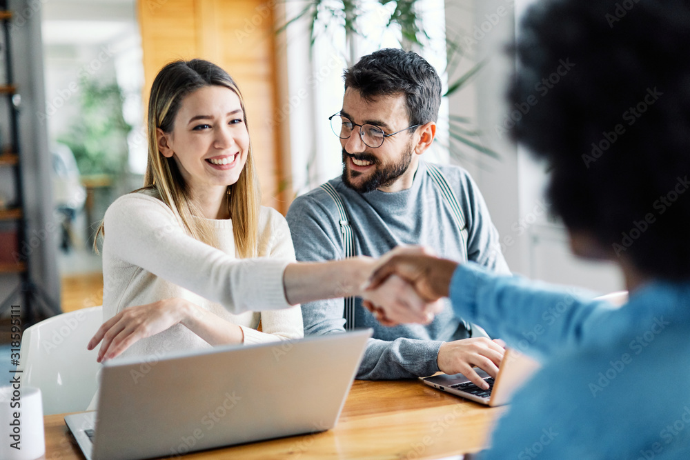 Fototapeta young couple shaking hands deal contract real estate investment