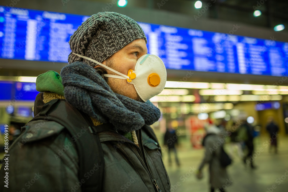 Fototapeta Man wearing a respirator mask device for health protection at an airport or railway train station in a crowd of people while travelling. Epidemic corona virus infection, flu sickness travel concept