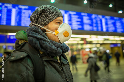 Cuadros en Lienzo Man wearing a respirator mask device for health protection at an airport or railway train station in a crowd of people while travelling