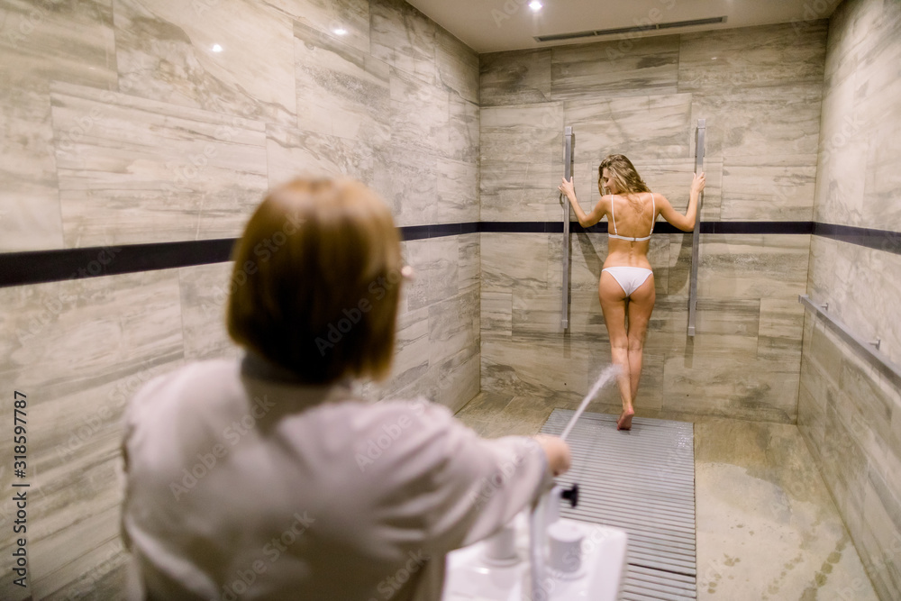 Fototapeta Pretty young woman having high pressure massage with Sharko shower in modern spa center. Woman therapist performing spa shower procedure for female client