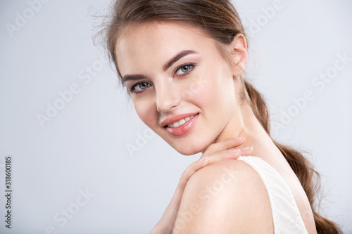 Fototapety, obrazy: Portrait of a smiling young woman with a brown hair.