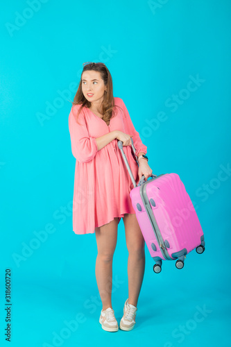 Fototapety, obrazy: Beautiful elegant woman in a pink dress with a pink big suitcase for travel on a blue isolated background