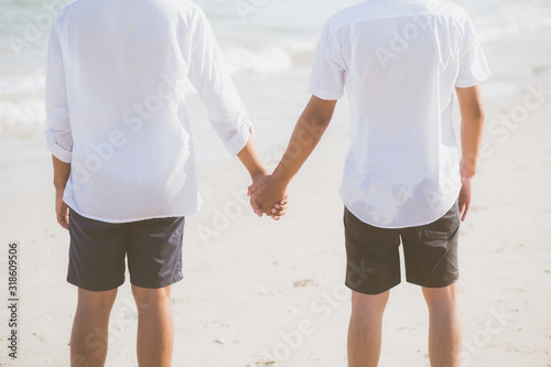 Closeup asian gay couple holding hands together on the beach with relax and leisure in summer, LGBT homosexual legal two man happy and romantic in vacation, relationship sex lover concept Canvas Print