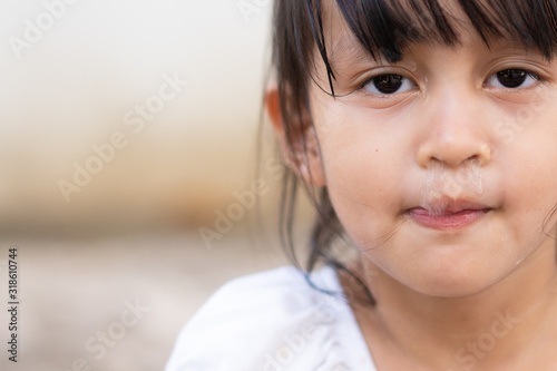 Photo Close up face of asian little girl with snot runny nose from common cold and allergy symptom, concept of health care in child and impact of health from viral and air pollution
