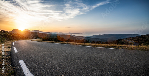 Empty long mountain road to the horizon on a sunny summer day at bright sunset Canvas Print