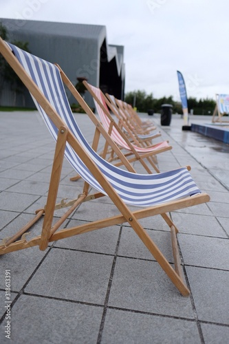 Empty Deck Chairs On Footpath In City Fotobehang