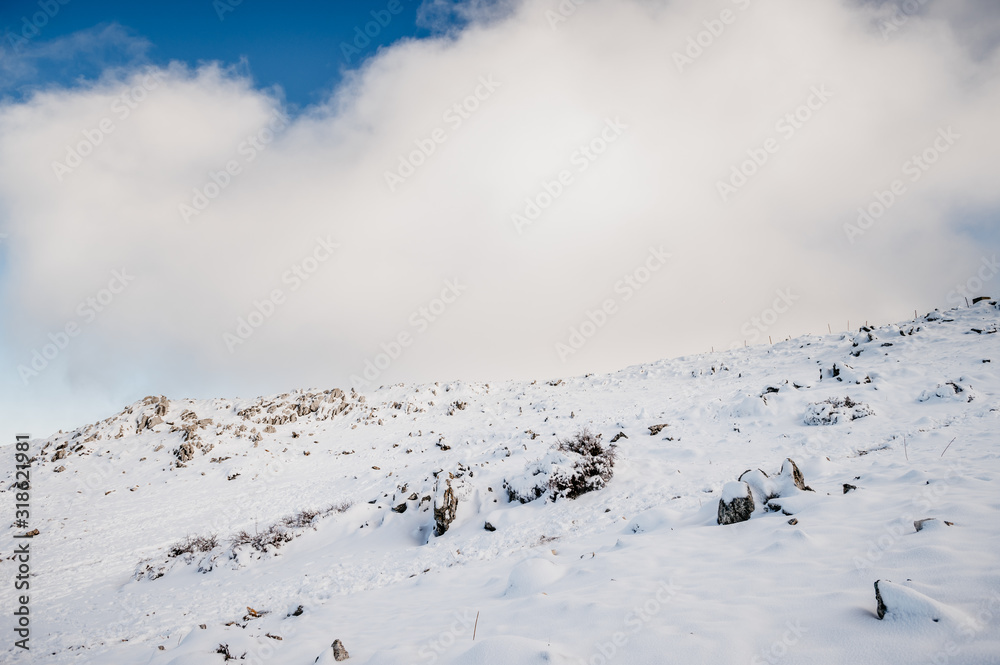 detail of a mountain slope with heavy snowfall and a blue sky full of thick clouds in the background