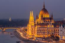 Illuminated Hungarian Parliament Building By Danube River At Night