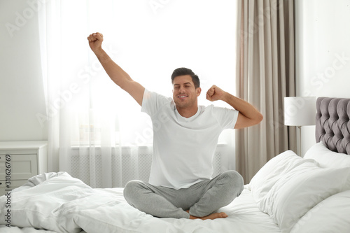 Man awakening on bed at home. Lazy morning Canvas Print