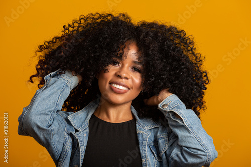 Young afro-american woman with curly hair looking at camera and smiling Canvas Print