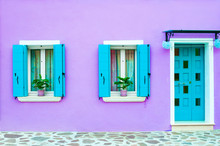 Blue Door And Windows With Blue Shutters On The Violet Facade Of The House. Colorful Architecture In Burano Island, Venice, Italy.