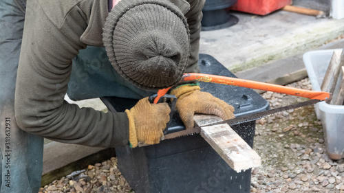 Valokuvatapetti Man using hacksaw to cut piece of wood